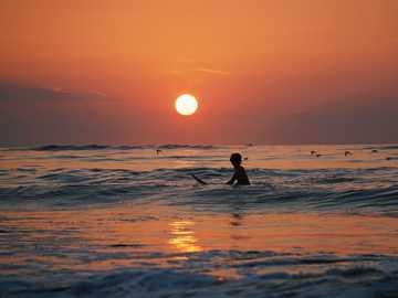 Ocean City surfing zachód słońca - zdjęcie sylwetki osoby jeżdżącej na desce surfingowej. Ocean City, Stany Zjednoczone