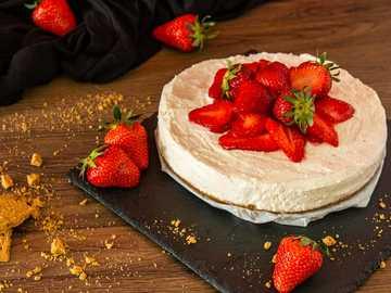 Niedzielny tort truskawkowy - truskawka na białym talerzu ceramicznym.