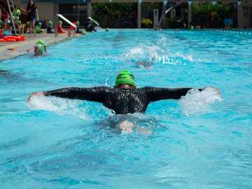 Natación mariposa - Hombre en traje negro de natación en la piscina durante el día.