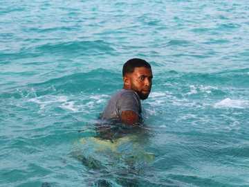 hombre negro dentro del mar - Hombre en camisa negra nadando en el agua durante el día. San Andrés, Santo André, Colômbia