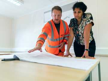 Female civil engineer discusses flood risk management with colleague - man in orange and white striped polo shirt beside woman in black and white floral dress.