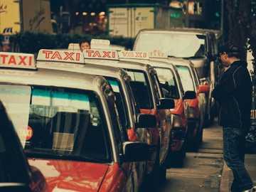 Hey Taxi - Person, die tagsüber in der Nähe eines geparkten Taxis steht. Hongkong
