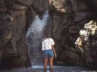 Frau im weißen Hemd, das vor Stürzen steht - Wenn Sie nicht müde werden, werden Sie nie die schönsten Orte auf dem Planeten Erde sehen. Viellei
