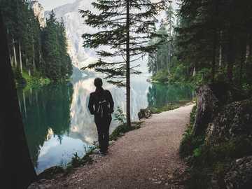 Na ścieżce nad jeziorem - osoba stoi w pobliżu jeziora. Lago di Braies, Włochy
