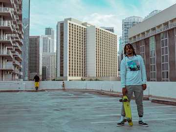 życie na deskorolce - mężczyzna w niebieskiej koszuli z długim rękawem i zielonych spodniach, stojący na szarej beton