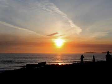 Menschen, die während der goldenen Stunde am Ufer stehen - Ein paar Leute bewundern den rauchigen Sonnenuntergang von den Klippen. Half Moon Bay State Beach, H