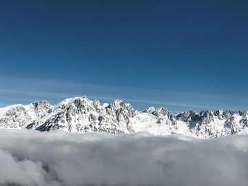 picos nublados - montaña cubierta de nieve bajo un cielo azul. Ellmau, Oostenrijk