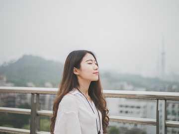 Kobieta z zamkniętymi oczami - kobieta zamykająca oczy biała stojąca na szynie ze stali nierdzewnej.