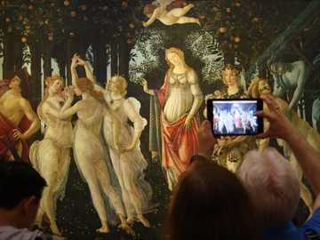 People in front of true Art - person taking a picture of a dancing women and men painting.