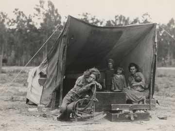 photographie en niveaux de gris de deux femmes avec trois enfants sous tente - Famille de travailleurs agricoles migrants. Sept enfants affamés. Mère âgée de trente-deux ans.