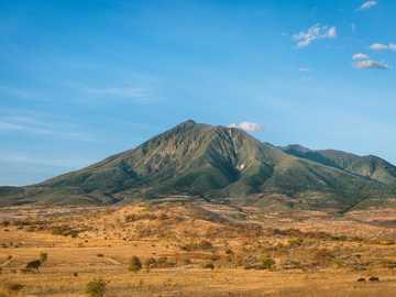 Zielona góra na sawannie - zdjęcie góry z ziemią brunatną w pobliżu. Mt. Hanang, Katesh, Tanzania