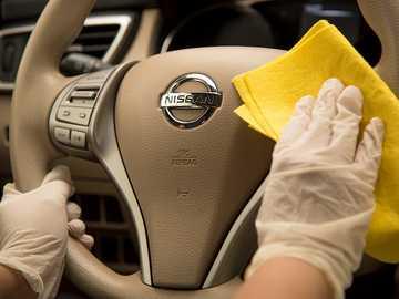 Dezinfekce aut - někdo dezinfikuje těsnění automobilu