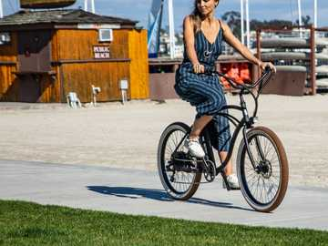woman riding bike - A Tower electric bike cruising along the boardwalk. .