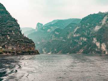 A view of Yangtze River, China - body of water in between mountains under white sky at daytime. Three Gorges Dam, Yichang Shi, China