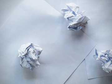 Papier brouillon et papier froissé - papier blanc sur des carreaux de sol blancs.