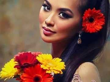 Kobieta o pięknych oczach z kwiatami w dłoniach - Kobieta o pięknych oczach z kwiatami w dłoniach