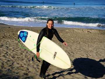 día placentero - mujer sosteniendo tabla de surf de pie en la orilla del mar. Seaside, Estados Unidos