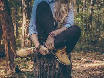 Kobieta zegarek na pniu - kobieta siedzi na pniu drzewa.
