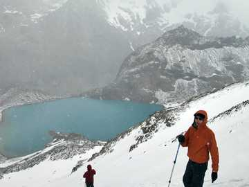 Hikers are descending after climbing in Patagonia - man in orange jacket and black pants walking on snow covered ground.
