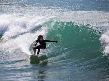 Surfear en Francia, en Bretaña - persona de negro surfeando las olas. Port Bara, Quiberon, Francia