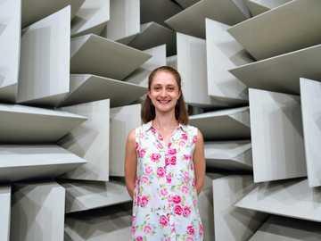 Ingeniero de ruido y vibraciones femenino en cámara anecoica - mujer en vestido sin mangas floral blanco y rosa de pie en escaleras de madera blancas.