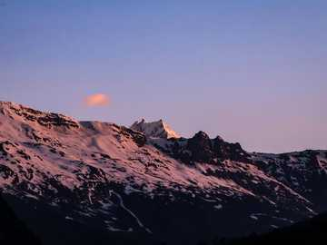 A sunset in Himachal Pradesh - summit view of mountain covered with snow under blue and white sky. Jispa, Himachal Pradesh, India