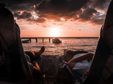 And the water caught fire. - two person lying on chaise lounge under sunset. Curaçao