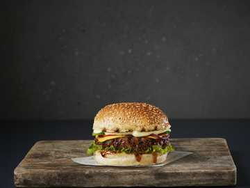 Burger Big Fry - burger na brązowej drewnianej desce do krojenia.