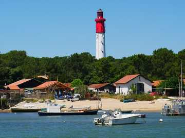 lighthouse in la conche du mimbault - white and red lighthouse near body of water during daytime. Cap Ferret, France