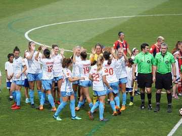 Programmation pour le début du jeu - équipe féminine de football debout sur le terrain avec des officiels et des enfants. Maryland Socc