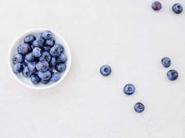 blueberries in bowl and white surface - The yummiest, juicy blueberries hand-picked at the local blueberry farm.