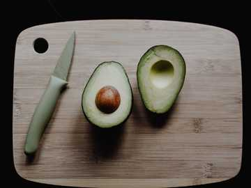sliced avocados on top of brown wooden chopping board in top view photography - It's not often you get such a good looking avocado in its' ripe window :).