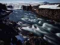 Godafoss waterfall - river near snow mountain. Godafoss, North Iceland, Iceland