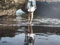 Junge Frau auf einem schwarzen Sandstrand, Bali Insel. - Person, die schwarzen Rucksack trägt, der auf Gewässer tritt. Bali, Indonesien