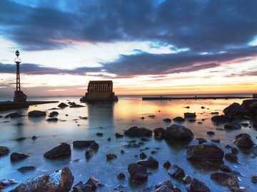 brown rocks on seashore during sunset - Un amanecer de hace unos años. Ya no existe esa estructura de hierro y cemento que aparece a la izq