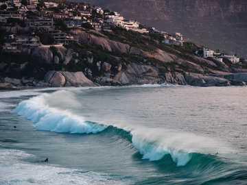 Ein gemütlicher Surfspot - Meereswellen, die tagsüber am felsigen Ufer abstürzen. Kapstadt, Süd Afrika