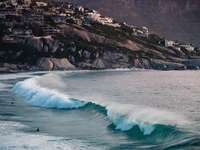 A cosy surfing spot - ocean waves crashing on rocky shore during daytime. Cape Town, South Africa