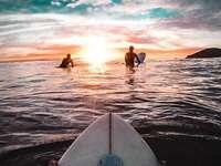 Väntar på den rätta vågen - Surfers väntar på den ideala vågen att klättra till det