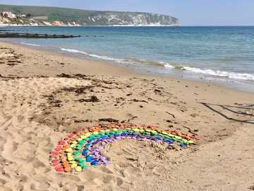 blue green and purple rubber band on beach shore during daytime - a rainbow on the beach for everyone. covid-19. postcard from the seaside during coronavirus . Swanag