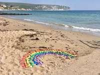 blaugrünes und lila Gummiband am Strandufer während des Tages - Ein Regenbogen am Strand für alle. Covid19. Postkarte vom Meer während des Coronavirus. Swanage, D