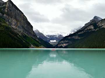 Boat on Lake Louise - person riding on canoe boat in between hill on body of water. Lake Louise, Canada