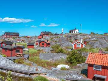 red houses under blue sky - Sunny beautiful but very windy day in Stockholms Archipelago. . Huvudskär, Stockholm, Sweden