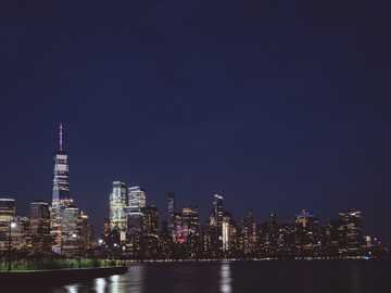 Waiting for fireworks - buildings beside sea during nighttime. New-York, Jersey city, USA