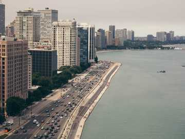Lake Shore Drive Summer - body of water beside buildings and road during daytime. North Lake Shore Drive, Chicago, United Stat
