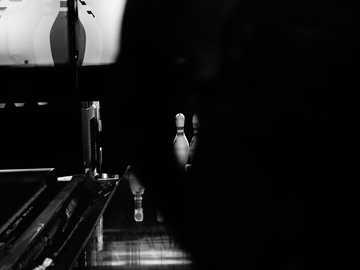 kręgle w ciemności - zdjęcie osoby stojącej w kuchni w skali szarości. Holandia