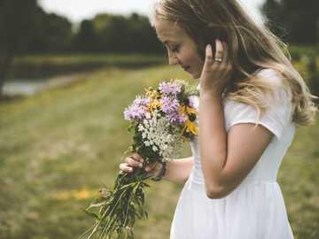Cedar Falls flowers - woman wearing white shirt holding flower wile smelling. Cedar Falls, United States