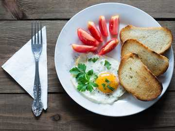 food on plate - fried eggs with toast and tomatoes on wooden table around fork.