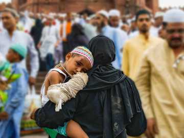 Mother's Love - woman holding a boy. Jama Masjid, New Delhi, India