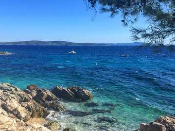 Clear waters at secluded shores of Ivan Dolac. - brown rocky shore with blue sea under blue sky during daytime. Ivan Dolac, Croatia