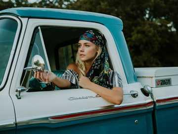 Ung blond kvinna som justerar vingspegeln - fotografi av kvinna med sidospegel i vit och grön 2-dörrars pickup.